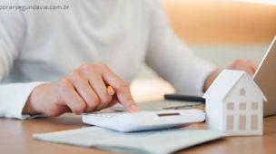Mão da pessoa na calculadora e usando computador calculando impostos, financiamento, da casa