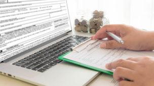 Pessoa com documento em papel preenchendo dados no laptop